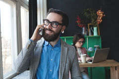 Businessman in glasses with smartphone over woman working on bac Royalty Free Stock Images