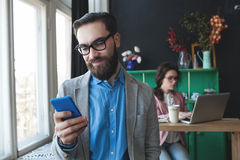 Businessman in glasses with smartphone over woman working on bac. Young businessman in glasses with smartphone over women working on laptop on background Stock Photo