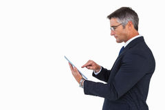 Businessman in glasses using his tablet pc Royalty Free Stock Photography