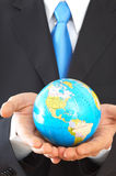 Businessman with globe. Businessman close up, holding mini globe, shallow dof stock image