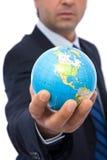 Businessman with globe. Businessman holding mini globe on white background stock images