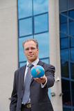 Businessman with globe in hand Royalty Free Stock Photos