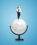 Businessman on globe Stock Photos