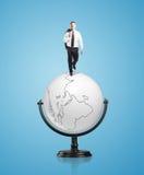 Businessman on globe Stock Photos