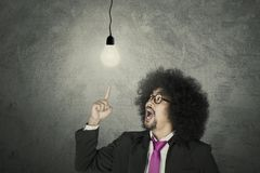 Businessman with glowing light bulb. Aha Moment: Businessman with glowing light bulb over grey background Stock Image