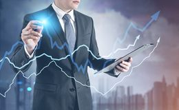 Businessman with a glowing pen, city grow graphs. Businessman with a glowing pen interacting with graphs. A foggy cityscape background. Toned image double Royalty Free Stock Photography