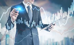 Businessman with a glowing pen, city and graphs. Businessman with a glowing pen interacting with graphs. A blurred cityscape background. Toned image double Royalty Free Stock Photography
