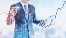 Businessman with a glowing pen, night city graphs. Businessman with a glowing pen interacting with graphs. A night cityscape background. Toned image double Royalty Free Stock Images
