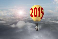 Businessman in glowing yellow lightbulb 2015 hot air balloon fly Stock Photos