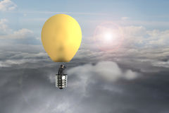 Businessman in glowing yellow lightbulb hot air balloon flying Royalty Free Stock Image