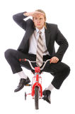 Businessman goes on children's bicycle Stock Image