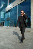 Businessman goes and speaks on  phone. Royalty Free Stock Images