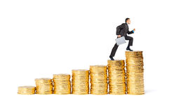 Businessman goes up the gold coins Stock Photos