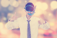 Businessman with goggles and blur background. Portrait of male entrepreneur wearing goggles and showing thumbs up, shot with bokeh background Royalty Free Stock Image