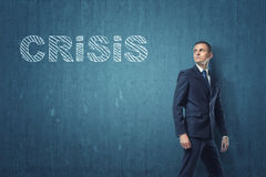 Businessman going away and turning around to look at the word `crisis` written on dark blue wall. A businessman going away and turning around to look at the Stock Image