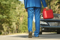 Businessman going the car to fill it. Businessman going to the car with jerrycan to fill it Royalty Free Stock Photos