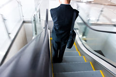 Businessman going down the escalator stock photo