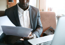 Businessman going through some documents at cafe Royalty Free Stock Image