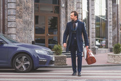 Businessman going on street with briefcase royalty free stock image