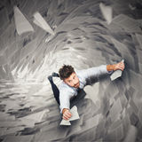 Businessman is going to fall. Businessman holding on to pieces of paper going to falling Stock Image