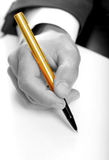 Businessman with gold pen. Businessman writing on a form. B/W & Gold pen royalty free stock photography