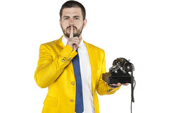 Businessman in a gold suit holding the telephone and asks for si. Business man in a gold suit holding the telephone and asks for silence Stock Photography