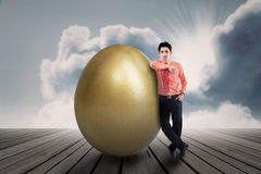 Businessman with golden egg outdoor Stock Images