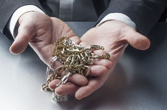 Businessman with golden and silver jewels in palms. Concept of business of appraiser or wealth in your hands royalty free stock photos