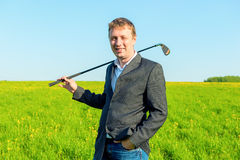 Businessman with a golf club in the field Stock Photos