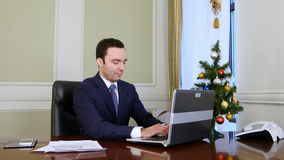 Businessman in a good mood working on laptop computer in the office. Professional shot in 4K resolution. 055. You can use it e.g. in your commercial video stock video