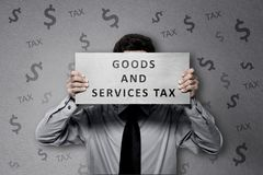 Businessman with Goods and services tax text on the paper Stock Image