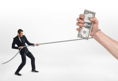 Businessman grabbed a big hand with cash dollars and pulls it by rope. Royalty Free Stock Images