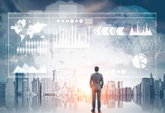 Businessman, graphs and city. Rear view of a businessman looking at a cityscape in front of him. Holograms of graphs in the sky. Elements of this image furnished Stock Photography
