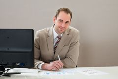 Businessman with graphs at desk Royalty Free Stock Photos