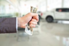 Businessman grasping money and giving away in showroom blurred b Stock Photos