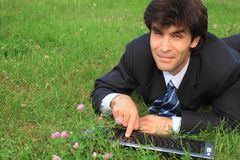 Businessman on grass with keyboard. Smiling businessman lies on green grass with laptop Royalty Free Stock Photography