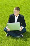 Businessman on grass with laptop, mixed feelings Stock Images
