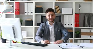 Businessman in gray jacket sitting at table in white office and rejoicing at success.