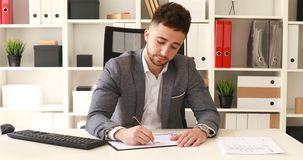 Businessman in gray jacket sitting at table in white office and writing on documents.