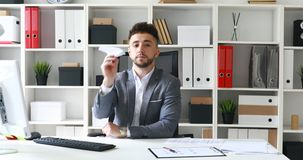 Businessman in gray jacket in white office and launching paper airplane
