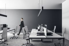 Businessman in gray office. Young businessman walking in gray coworking office interior with furniture and daylight. Workplace concept royalty free stock photography