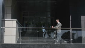 The businessman in a gray suit and sunglasses is appearing on the porch of the business center. A man is takes off sunglasses confidently looking forward stock video