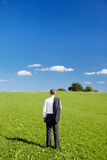 Businessman in a green field. Standing with his back to the camera and jacket slung over his shoulder looking out over the countryside Royalty Free Stock Image