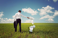 Businessman in a green field throws papers in the trash. Businessman in a green field with a blue sky throws papers in the trash Royalty Free Stock Photo