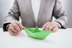 Businessman with a green paper boat Royalty Free Stock Photos