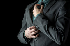 Businessman in green shirt and suit adjusting his black necktie Royalty Free Stock Images