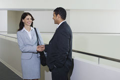 Businessman Greeting Female Colleague In Office. Happy African American businessman greeting female colleague in office stock photography