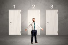 Businessman thinking in front of three doors Stock Image