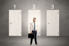 Businessman thinking in front of three doors Royalty Free Stock Photo