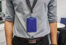 Businessman with grey shirt and neck company badge in office royalty free stock photography